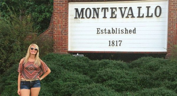 Ashlin Bohl stands by a Montevallo campus sign